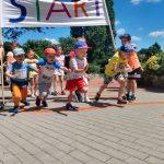 Czworo dzieci ustawionych na linii startu rozpoczyna bieg. Dzieci ustawione z tyłu kibicują kolegom i koleżankom