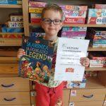 Chłopiec wyróżniony w konkursie, stoi trzymając dyplom dla przedszkola i nagrodę książkową.